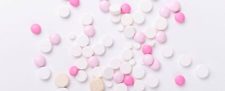 Pink and white pills on white background. Heap of assorted various medicine tablets and pills. Health care. Copy space. Top view. Horizontal banner