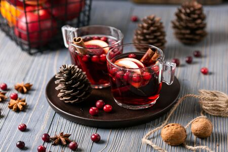 Mulled wine in glasses on a wooden background. Apples, cranberries, cinnamon, star anise, walnuts, cones Imagens