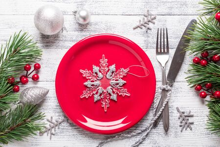 Christmas table setting with red plate and silverware on light wood background. Fir tree branch, holly berries. Top view with copy space.