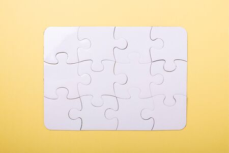 Puzzle pieces on yellow background White puzzle Concept success of business Top view