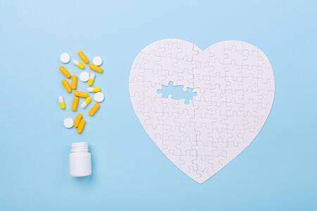 Puzzle in shape of heart white and yellow pills on blue background Concept treatment of heart disease pills Jigsaw Top view Copy space
