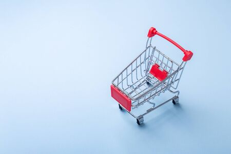Mini trolley cart copy on blue background Top view Copy space - Image