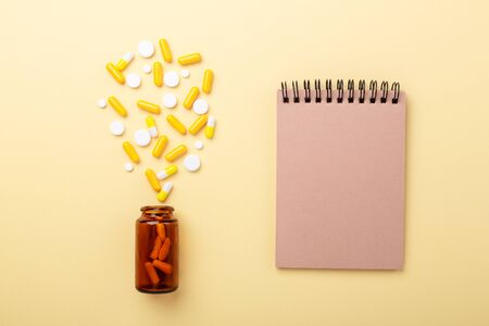 Multicolor tablets and pills capsules from glass bottle on yellow background Notebook Heap of assorted various medicine tablets and pills. Health care. Copy space. Top view.