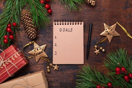 Fir branches, gifts and an notebook on a wooden background. New goals. Christmas background. Top view, copy space - Image