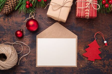 Christmas greeting card with fir tree branch, gifts, present box and envelope. Wooden background Top view, copy space.