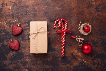 Christmas composition with candy canes, present box and gifts. Red and craft decoration on wooden background. New Year concept. Top view - Image