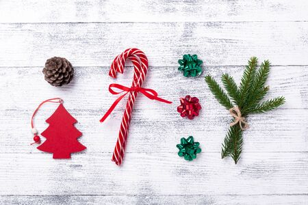 Christmas composition. Red gifts, fir tree, fir branch and cone, candy canes on wooden background. Flat lay, top view - Image Zdjęcie Seryjne