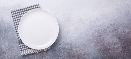 Empty white plate and linen napkin on stone background Copy space Top view Horizontal banner - Image