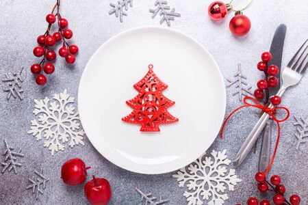 Christmas table place setting with empty white plate, cutlery with festive decorations star bow ball deer on stone background. Christmas and New Year holiday concept - Image