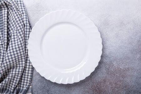 Empty white plate and linen napkin on stone background Copy space Top view - Image Zdjęcie Seryjne
