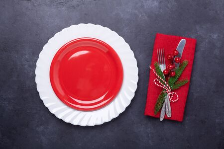 Christmas table place setting with empty red plate, cutlery with festive decorations snowflake star bow ball on stone background. Christmas and New Year holiday concept - Image