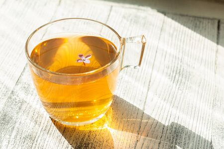 Cup of herbal tea on wooden background. Glass cup. Rays of sunlight - Image Archivio Fotografico - 133359623