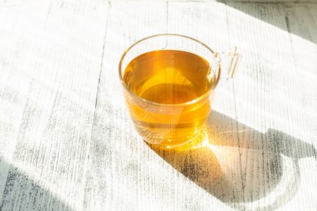 Cup of herbal tea on wooden background. Glass cup. Rays of sunlight - Image Archivio Fotografico - 133359620