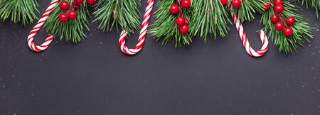 Christmas background with tree branches, candy cane and holly on black wooden background. Snowfall drawing effect. Horizontal banner. Top view Copy space - Image