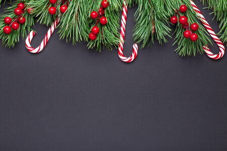 Christmas background with tree branches, candy cane and holly on black wooden background. Horizontal banner. Top view Copy space - Image