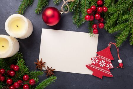 Merry Christmas card with paper, gift box and fir tree branch on stone background. Red accessories. Top view- Image