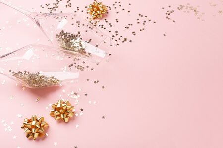 Christmas flat lay. Champagne glasses and gold decoration on pink background - Image