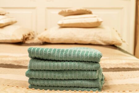 Stack of green hotel towel on bed in bedroom interior - Image Фото со стока