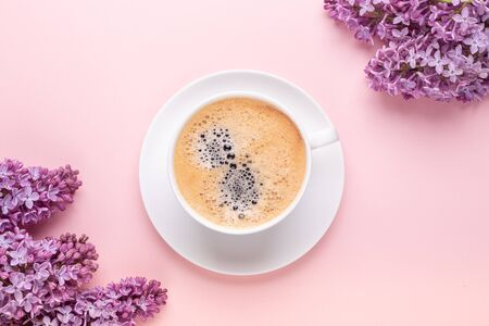 Lilac and cup of coffee on pink background. Still life. Spring romantic mood. Top view. Copy space - Image