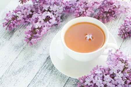 Cup of herbal tea and lilac on wooden background. Rays of sunlight - Image Standard-Bild