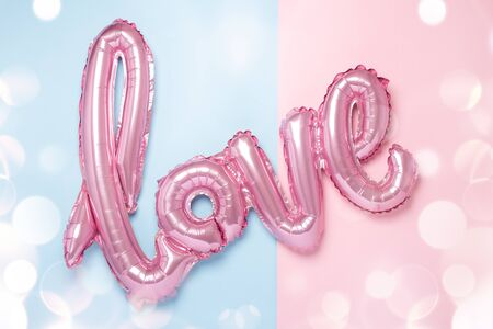 Pink balloons in the form of word Love on pink and blue background. Valentines day celebration. Bokeh effects - Image Stock Photo