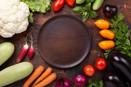 Brawn wood plate and fresh farmers garden vegetables on wooden table. Harvest time. Top view - Image Reklamní fotografie