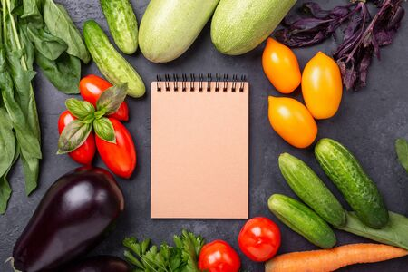 Assorted raw organic vegetables and craft notebook on dark stone background Harvest time Vegetarian eating and dieting concept Top view Copy space