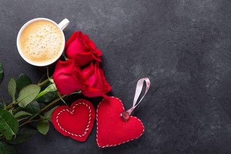 Valentines day greeting card. Coffee cup, red roses and textile hearts on stone background. Top view - Image Reklamní fotografie
