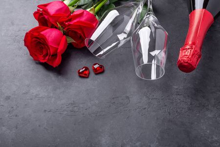 Valentines day greeting card. Red roses, champagne, glasses on stone background. Top view- Image