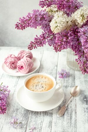 Cup of coffee, homemade marshmallow, lilac flowers. Romantic spring morning Selective focus - Image Standard-Bild