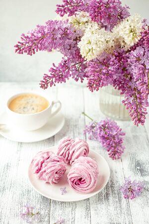 Flieder, Kaffee und hausgemachter rosa Eibisch auf weißer Keramikplatte. Romantischer Frühlingsmorgen. Selektiver Fokus - Bild Standard-Bild