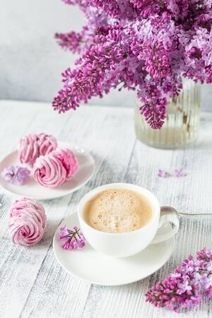 Bouquet of lilacs, cup of coffee, homemade marshmallow Romantic spring morning Selective focus - Image