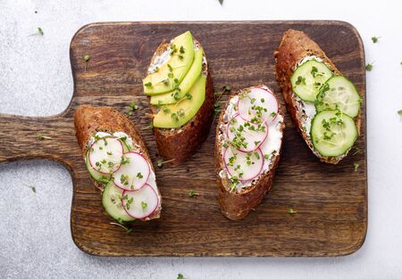 Vegetarian sandwiches on a wooden board. Cream cheese, avocado, cucumber, radish and mustard micro greens. Top view. Healthy snack - Image Standard-Bild