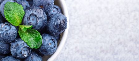 Fresh ripe and juicy blueberries with drops of water. White bowl. Mint leaf. Copy space. Macro photo - Image Banque d'images