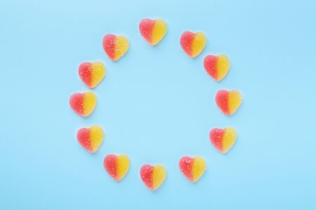 Colorful gummy hearts on blue background. Jelly sweets in circle shaped. Top view - Image Фото со стока