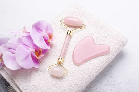 Gua Sha massager and face roller on stone background. Massage tool for facial skin care, SPA beauty treatment concept - Image