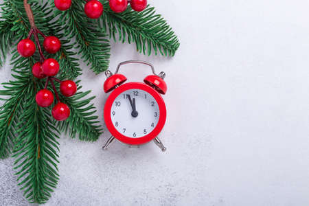 Christmas composition with red alarm clock, fir tree branches and holly on stone background. New Year concept. Top view. Copy space - Image
