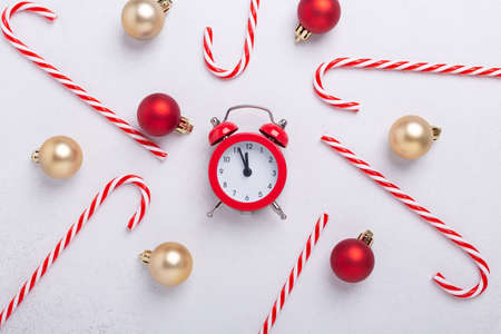 Christmas composition with candy canes, red alarm clock and christmas balls on white background. New Year concept. Top view - Image