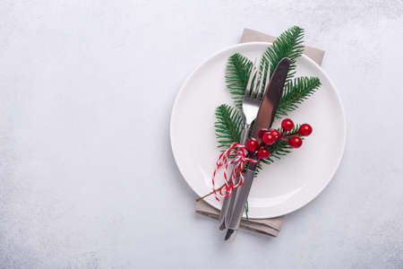 Christmas table place setting with empty white plate, candy canes, fir branch and cutlery with festive decorations on stone background - Image