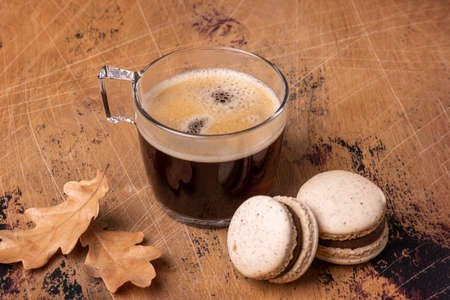 Glass cup of coffee and chocolate macarons on wooden background. Cozy autumn composition - Image Stock fotó