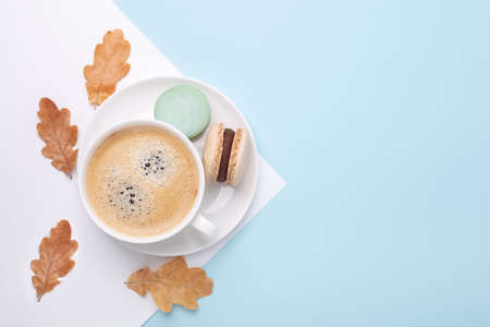 Creative autumn flat lay. Cup of coffee, macarons and oak leaves on blue background - Image Stock fotó