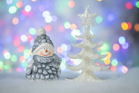 Christmas greeting card with decorative cute snowman and white fir tree. Bokeh effect on background - Image
