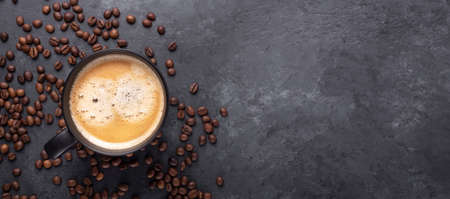 Horizontal banner with cup of coffee and coffee beans on dark stone background. Top view. Copy space - Image