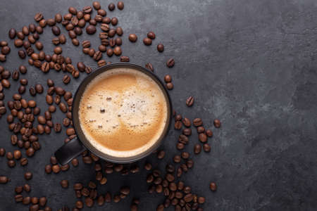 Cups of coffee and coffee beans on dark stone background. Top view. Copy space - Image