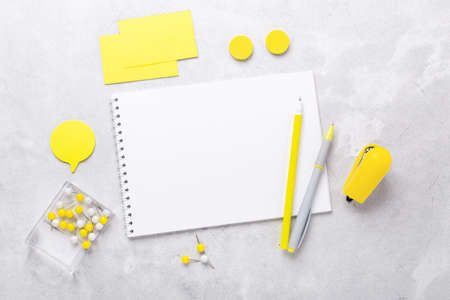 Office workplace with notepad and stationery accessories on gray stone background. Yellow stationery. Flat lay. Top view - Image