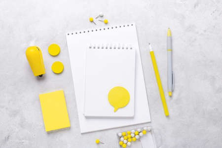 Top view of workspace with notepad and stationery accessories on gray stone background. Illuminating Yellow and Ultimate Gray, colors of the year