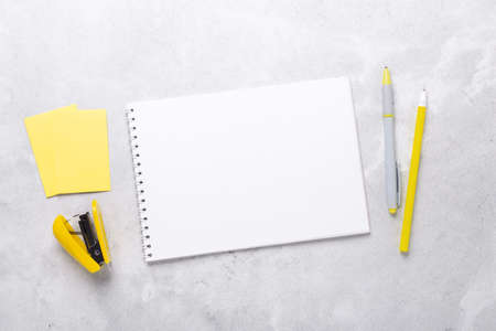 Gray workspace with notepad and yellow stationery accessories. Illuminating Yellow and Ultimate Gray, colors of the year