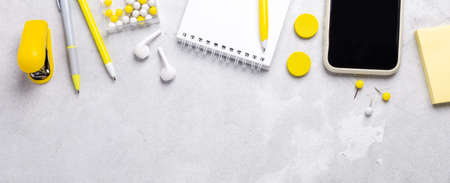 Horizontal banner with smartphone, notepad and yellow stationery accessories on gray stone background. Illuminating Yellow and Ultimate Gray, colors of the year 版權商用圖片