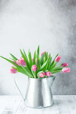 Spring floral background. Pink tulip flowers bouquet on shelf in front of stone wall. Copy space - Image