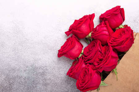 Craft paper shopping bag with flowers on stone background. Red roses in a brown kraft bag. Copy space - Image 版權商用圖片